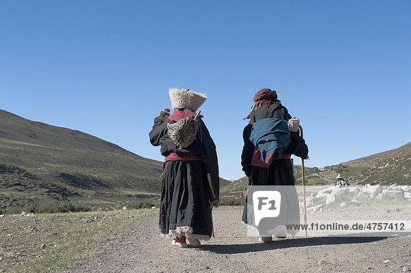 Tibetischer Buddhismus  Pilgerinnen wandern nahe dem Kloster Zutul Puk Gompa  in Tracht gekleidet  Pilgerweg um den heiligen Berg Kailash  Gang Rinpoche  Kora  Ngari  Gang-Tise-Gebirge  Transhimalaja  Himalaja  Westtibet  Autonomes Gebiet Tibet  Volksrepublik China  Asien