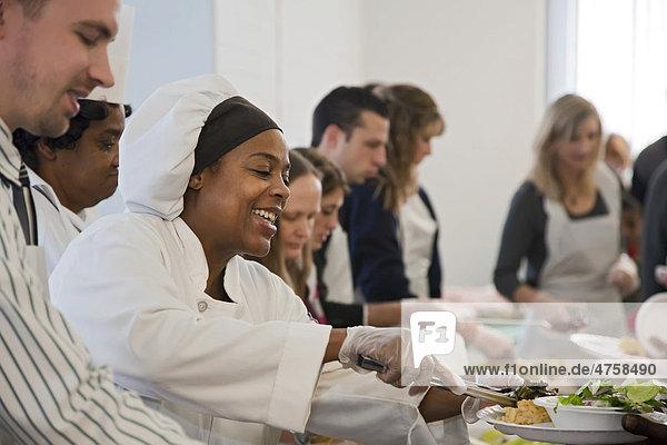 Studenten der Dorsey Kochschule servieren Obdachlosen und Unterstützern  die sich in der Cathedral Church of St Paul für den Homeless Persons' Memorial Day versammelt haben  eine Mahlzeit  damit wird Obdachlosen gedacht  die im vergangenen Jahr verstarben  Detroit  Michigan  USA