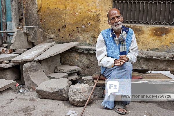 Ein älterer Mann  Rajasthani  Inder ruht sich vor einem Haus auf einer Steinbank mit Sitzkissen aus  Bundi  Rajasthan  Indien  Asien