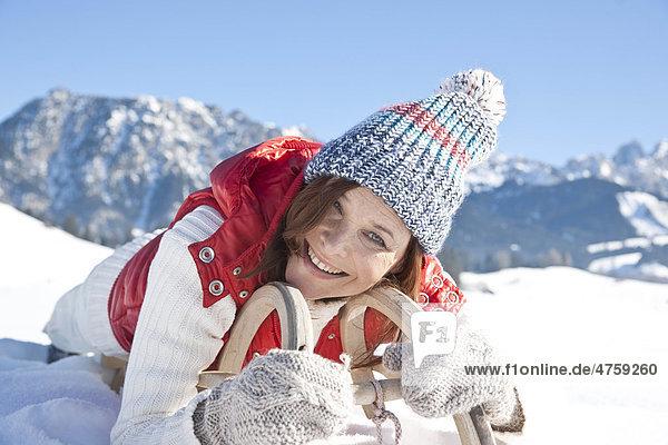 Lächelnde Frau liegt auf einem Schlitten  Tannheimer Tal  Tirol  Österreich