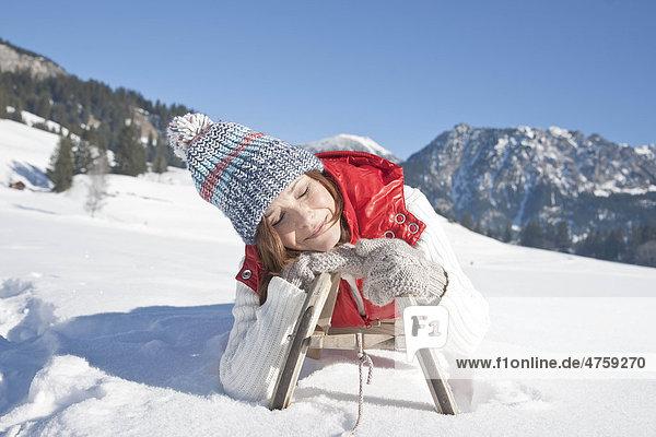 Smiling woman lying on toboggan  Tannheimer Tal  Tyrol  Austria