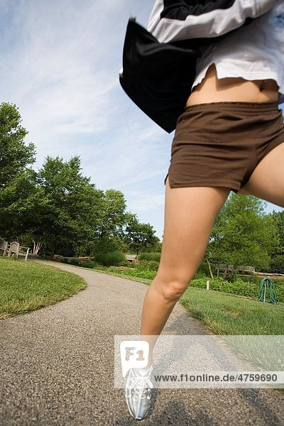 Young woman in early 20s jogging in park
