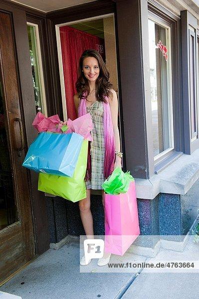 Woman in urban setting carrying shopping bags