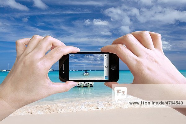Close up photo of a woman taking photos of beautiful beach with her iPhone 4