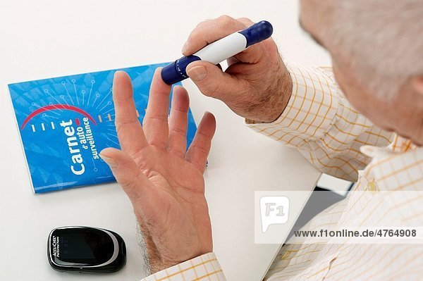 Diabetic Senior man making a blood test  to check his Hypoglycemia with a meter