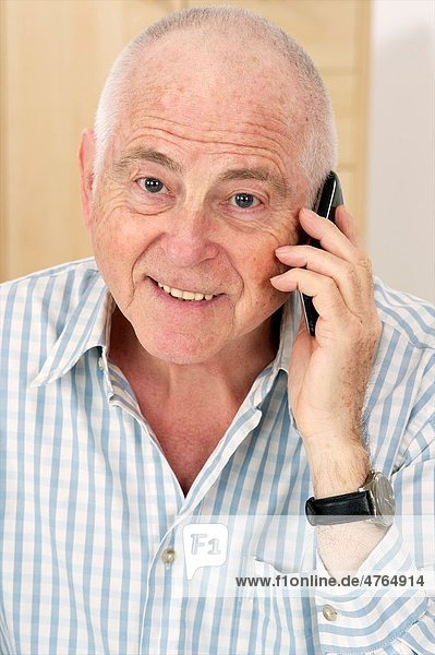 Senior man using a cell phone looking happy