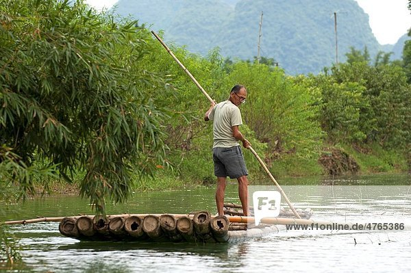 Man standing on a bamboo raft and rowing along the Yulong River  Yangshuo  Guangxi  China