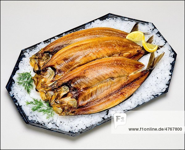 Kipper smoked Herring fishes on platter with ice