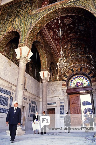 People walking under a decorative ceiling while entering the Umayyad Mosque  Damascus  Syria