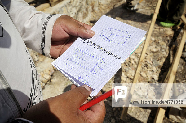 Architect holding the diagram of a wooden house. After the massive earthquake in January 2010 a German aid organizations is training local construction workers  here in the construction of earthquake-proof houses  Coq Chante village near Jacmel  Haiti  Caribbean  Central America