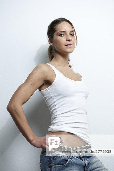 Sportliche junge Frau in weißem Shirt und Jeans