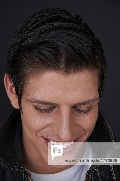 Junger Mann mit strahlend weißen Zähnen lächelt  Porträt