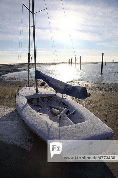 Bucht im Wattenmeer mit Segelboot  verschneiter Strand auf der ostfriesischen Nordseeinsel Spiekeroog  Niedersachsen  Deutschland  Europa