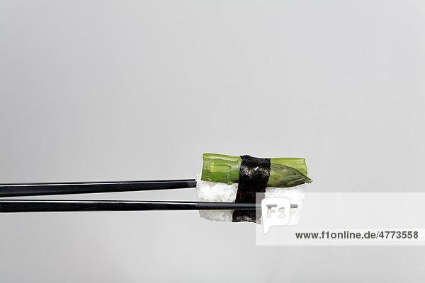 Schwarze Essstäbchen halten Nigiri-Sushi mit grünem Spargel  umwickelt mit Nori