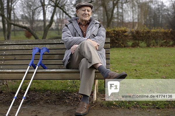 Alter Mann  Senior  92 Jahre  auf einer Bank  mit Krücken