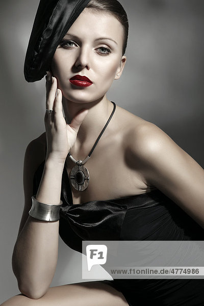 Junge Frau mit eleganter Mütze und schwarzem Kleid  Porträt
