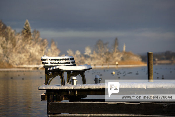 Snow on bench seat and old wooden pier  lake Chiemsee  Chiemgau  Upper Bavaria  Germany  Europe