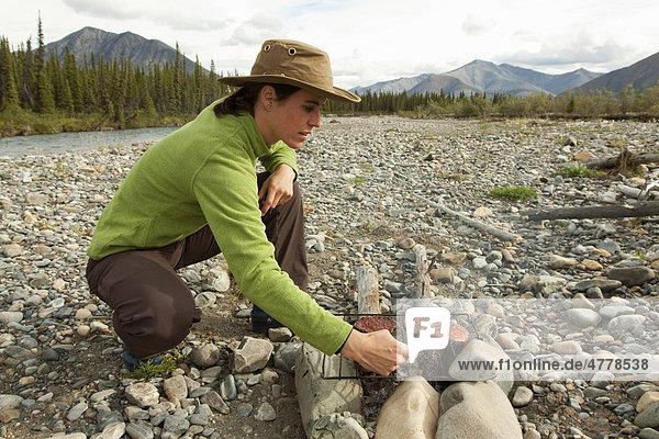 Junge Frau kocht auf einem Lagerfeuer  grillt Hamburger  Kiesbank  Wind River  Yukon Territory  Kanada