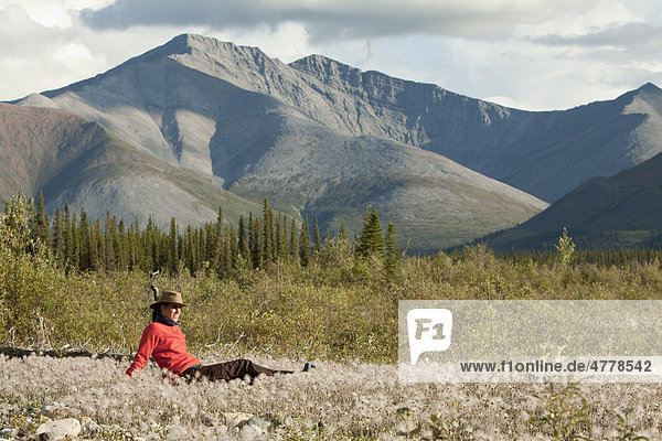 Junge Frau sitzt entspannt im Gras  Wollgras  und genießt die Abendsonne  Northern Mackenzie Mountains  Wind River  Yukon Territory  Kanada