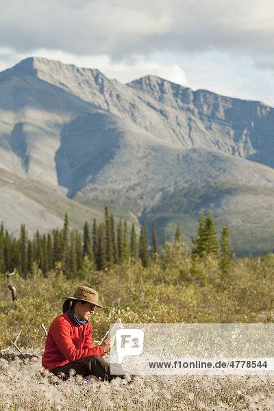Junge Frau sitzt entspannt im Gras  Wollgras  und liest ein Buch  Northern Mackenzie Mountains  Wind River  Yukon Territory  Kanada