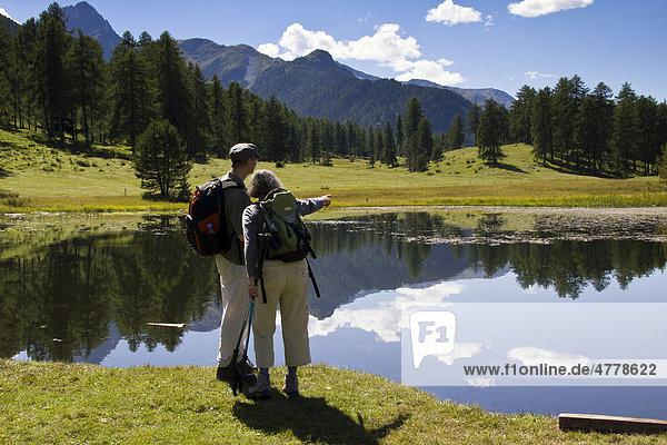Wanderer in der Hochmoorebene mit dem schwarzen See Lai Nair bei Tarasp und Vulpera  Scuol  Unterengadin  Graubünden  Schweiz  Europa