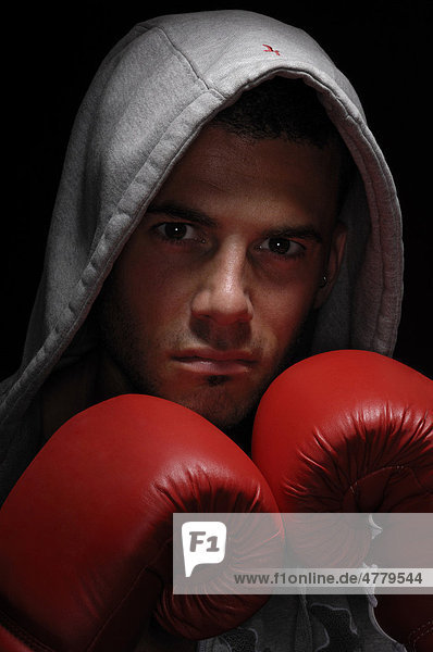 Junger Mann  Kickboxer  mit Kapuze und roten Boxhandschuhen  Porträt