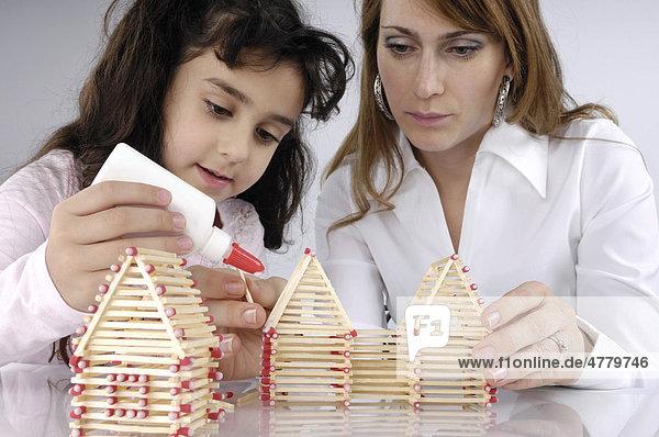 Mutter und Tochter bauen ein Haus aus Streichhölzern