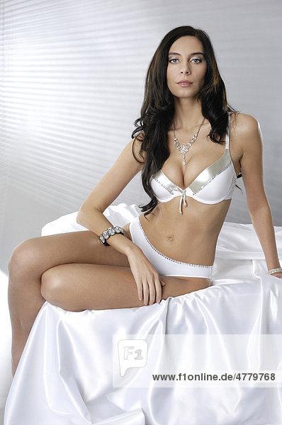 Junge Frau in weißen Dessous sitzt auf einem Bett