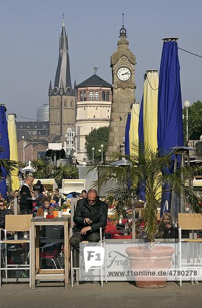 Rheinpromenade mit Restaurants  Pegeluhr  Schlossturm und St. Lambertus-Kirche  Düsseldorf  Nordrhein-Westfalen  Deutschland  Europa