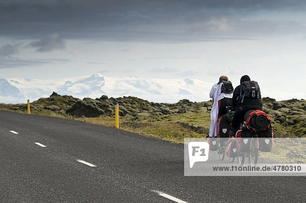 Two bikers cycling along the southwest coast  Iceland  Scandinavia  Europe