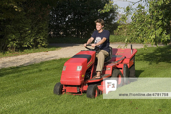 Mann auf fahrbarem Mäher mit Benzinmotor beim Rasenmähen
