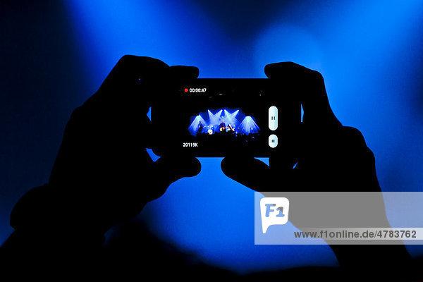 Konzertbesucher macht ein Foto mit iPhone