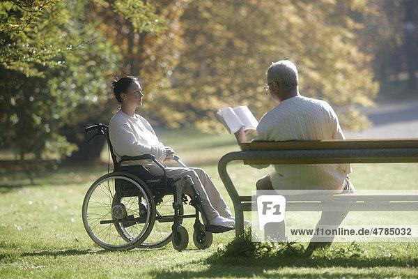 Frau sitzt im Rollstuhl  Mann sitzt mit Buch auf Parkbank
