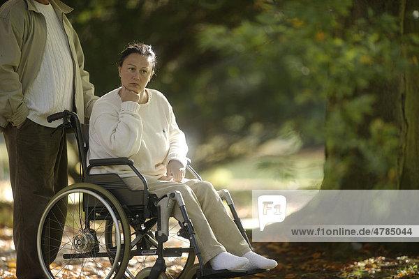 Frau sitzt nachdenklich im Rollstuhl  Mann steht daneben