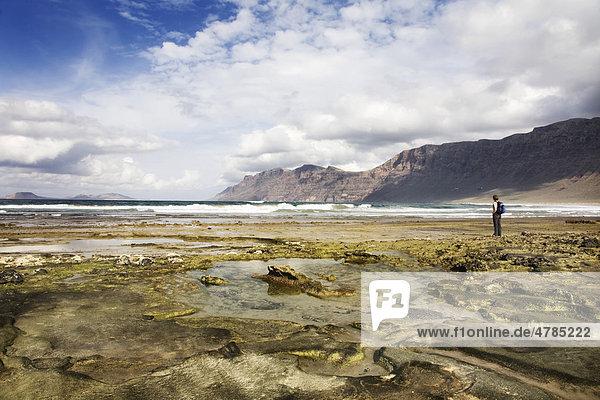 Frau steht am Famarastrand  hinten das Famaramassiv  Lanzarote  Kanarische Inseln  Spanien  Europa