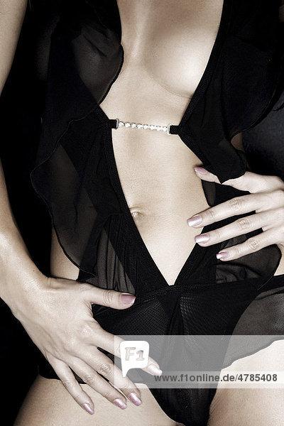 Torso  junge Frau mit schwarzem Oberteil  Detail Brust  Bauch und Hände