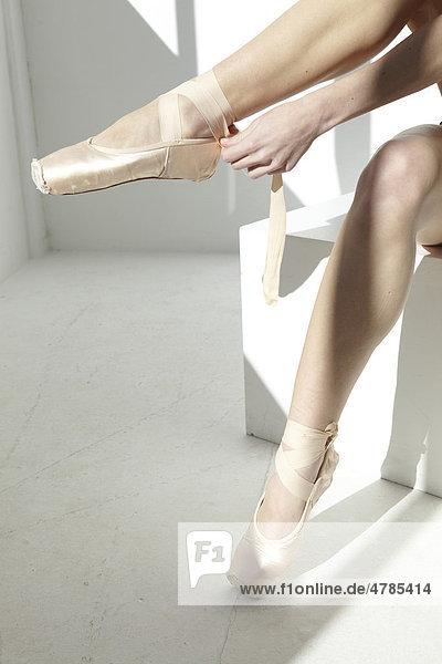 Balletttänzerin zieht Ballettschuhe an in weißem Raum  Ausschnitt Schuhe und Hand
