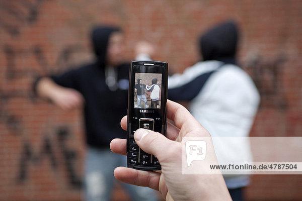 Zwei Jungen prügeln sich auf dem Schulhof und werden dabei von einem dritten mit seinem Handy gefilmt  gestellte Szene