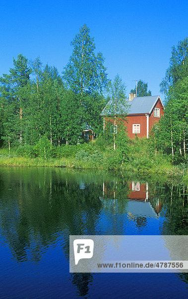 Rotes Holzhaus an einem idyllischen See bei Särna  Schweden  Skandinavien  Europa Holzhaus