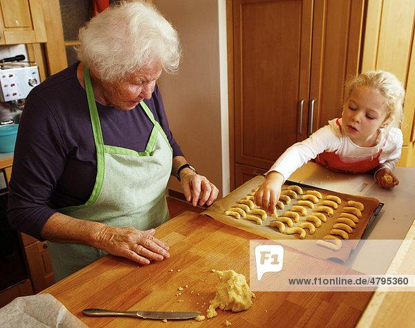 Weihnachtsbäckerei  Oma und Enkelin backen Weihnachtsplätzchen  Mädchen legt Teig aufs Backblech