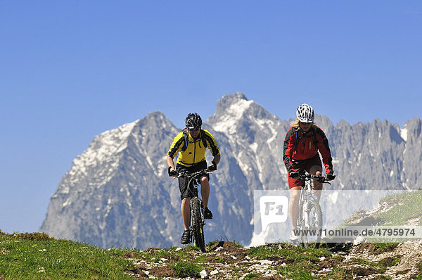 Mountain bikers on the Eggenalm alpine pasture in front of the Wilder Kaiser Mountains  Reit im Winkl  Bavaria  Germany  Tyrol  Austria  Europe