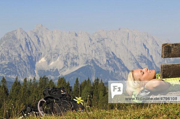 Wanderin ruht sich aus  Eggenalm beim Straubinger Haus  hinten der Wilde Kaiser  Reit im Winkl  Chiemgau  Oberbayern  Bayern  Deutschland  Tirol  Österreich  Europa