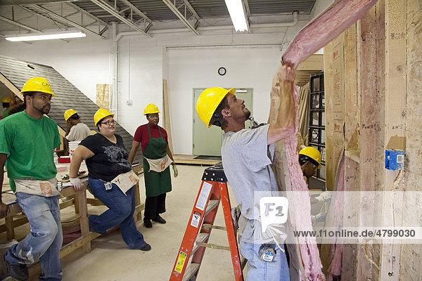 Eine Gruppe benachteiligter Menschen lernt mit Dämmstoffen zu arbeiten  als Teil ihrer Ausbildung für Wärmeisolierung  Wetterschutz und andere grüne  umweltfreundliche Berufe  Anti-Armuts-Programm gefördert von einem föderalen Konjunkturprogramm  Detroit  Michigan  USA  Amerika