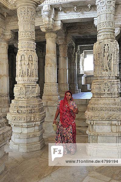 Junge indische Frau im traditionellen Sari in der Innenhalle mit kunstvoll verzierten Säulen im Marmortempel Ranakpur  Tempel der Jain-Religion  Rajasthan  Nordindien  Indien  Asien