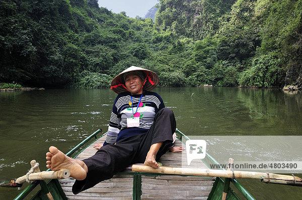 Frau rudert mit Füßen,  Umgebung von Ninh Binh,  unterwegs am Fluss zu den Höhlen von Trung Anh,  trockene Halong Bucht,  Vietnam,  Südostasien
