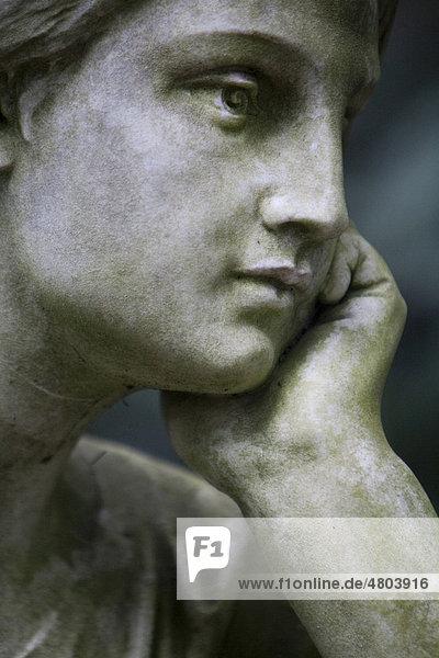 Frau stützt Kopf auf Hand  Figur  Portrait  Friedhof