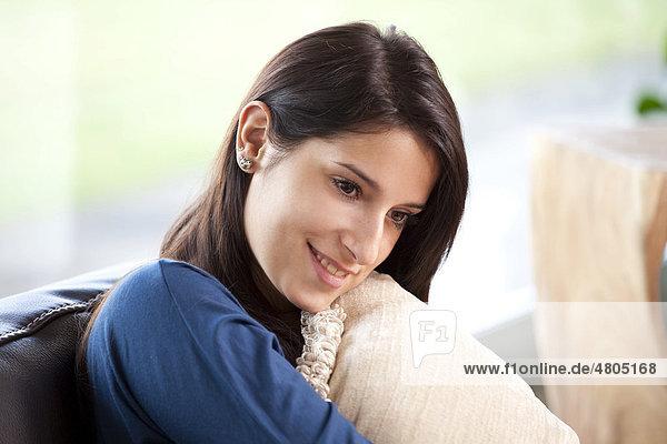 Junge Frau sitzt entspannt auf einem Sofa mit Kissen im Arm
