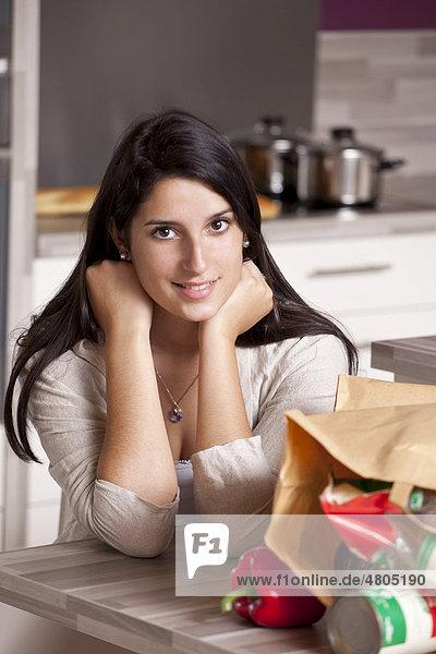 Junge Frau sitzt in der Küche am Esstisch  im Vordergrund eine Papiertüte mit Einkäufen
