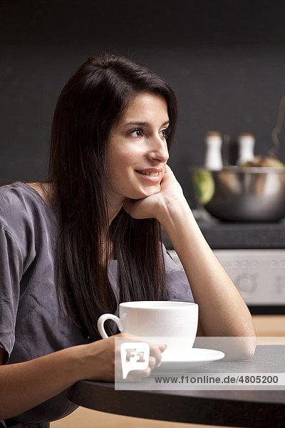 Junge Frau sitzt in der Küche und trinkt Kaffee