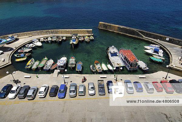 Geparkte Autos und Fischerboote im Hafen  Marsalforn Bay Bucht  Marsalforn  Insel Gozo  Malta  Mittelmeer  Europa